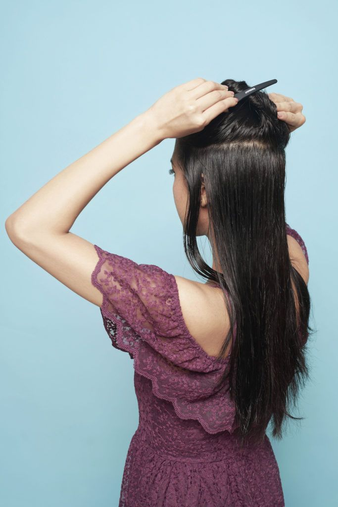Asian woman clipping a section of her hair