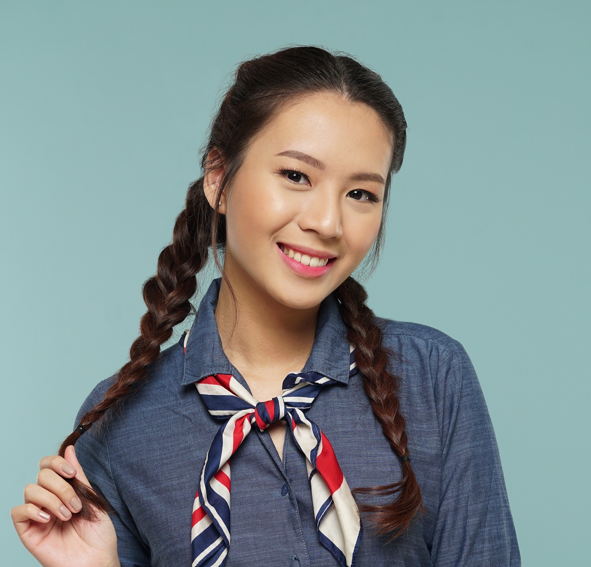 Dutch braid: Closeup shot of an Asian woman with long dark hair in messy two braids wearing a denim dress