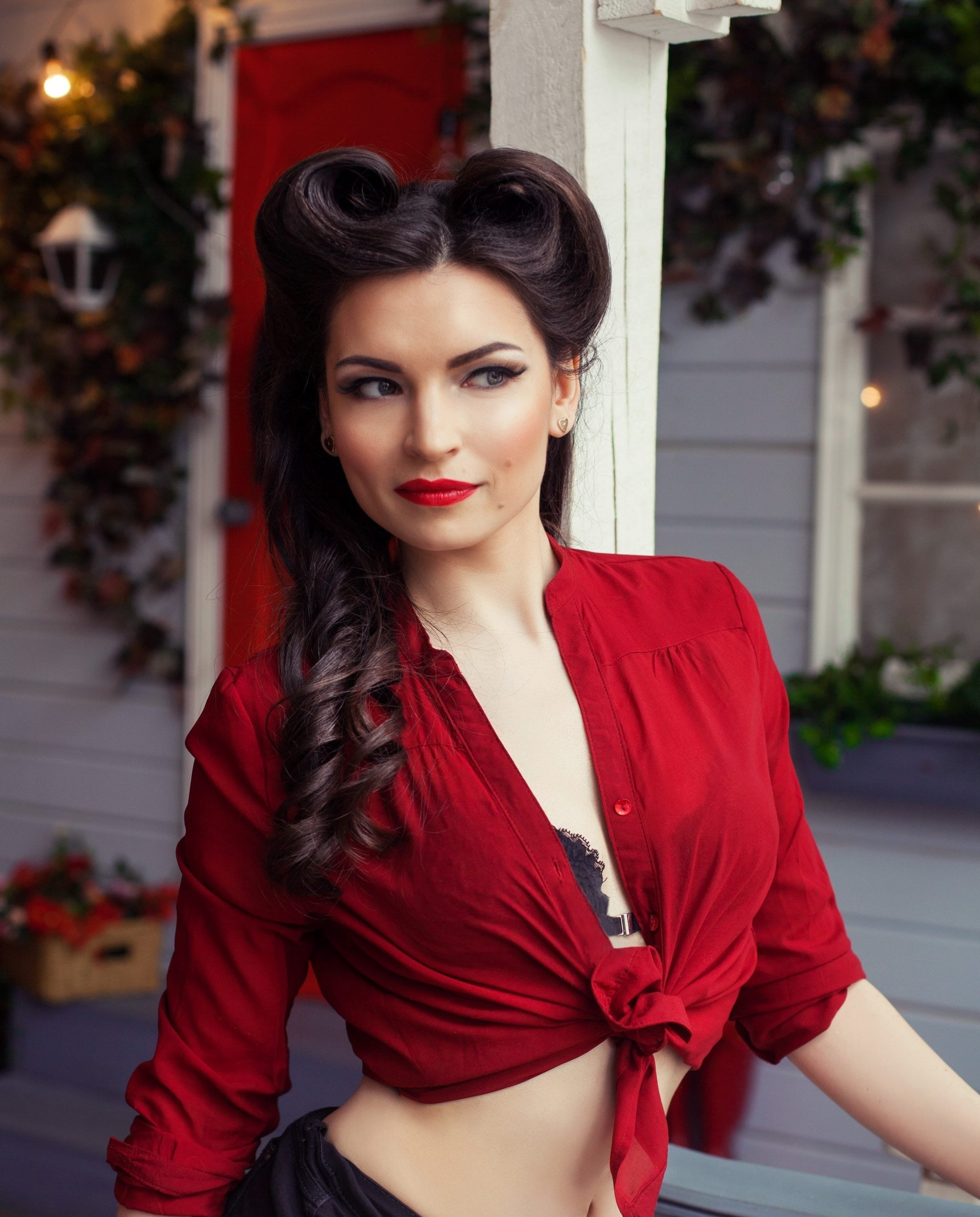 Rockabilly hair: Woman with long hair in a twisted long rockabilly hairdo wearing a red cropped top