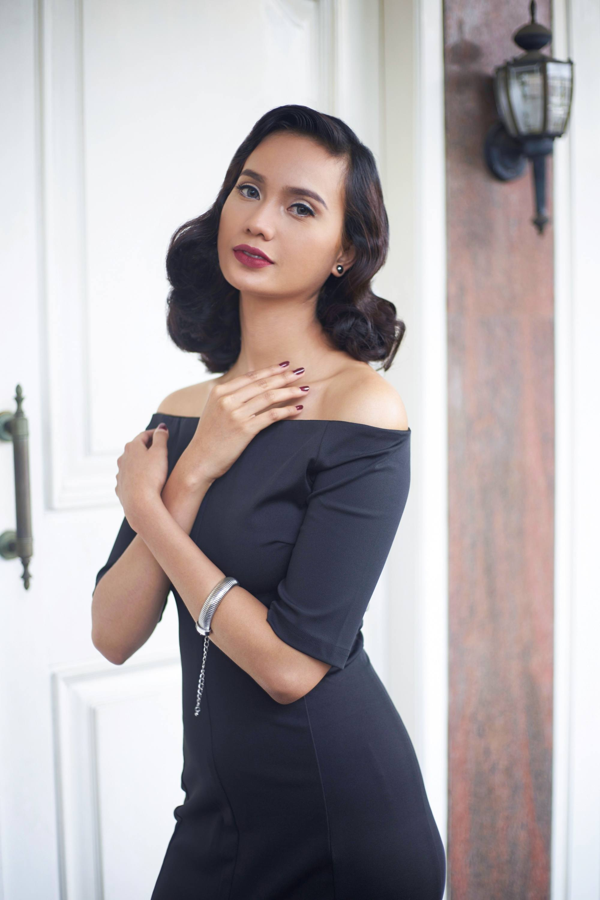 Asian woman with dark shoulder-length curly hair wearing an off-shoulder dress