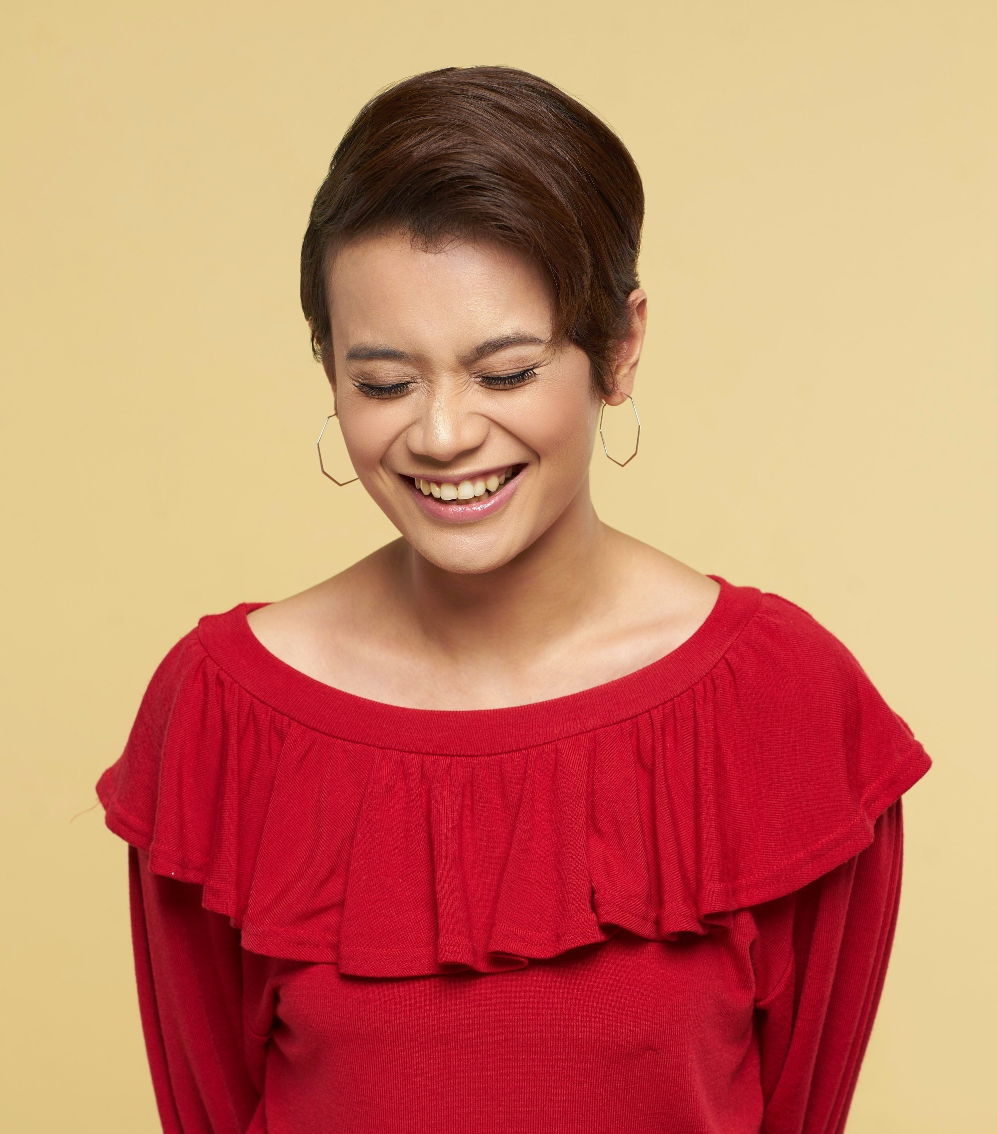 Short hairstyles for Filipinas: Closeup shot of an Asian woman with sleek pixie cut wearing a red blouse