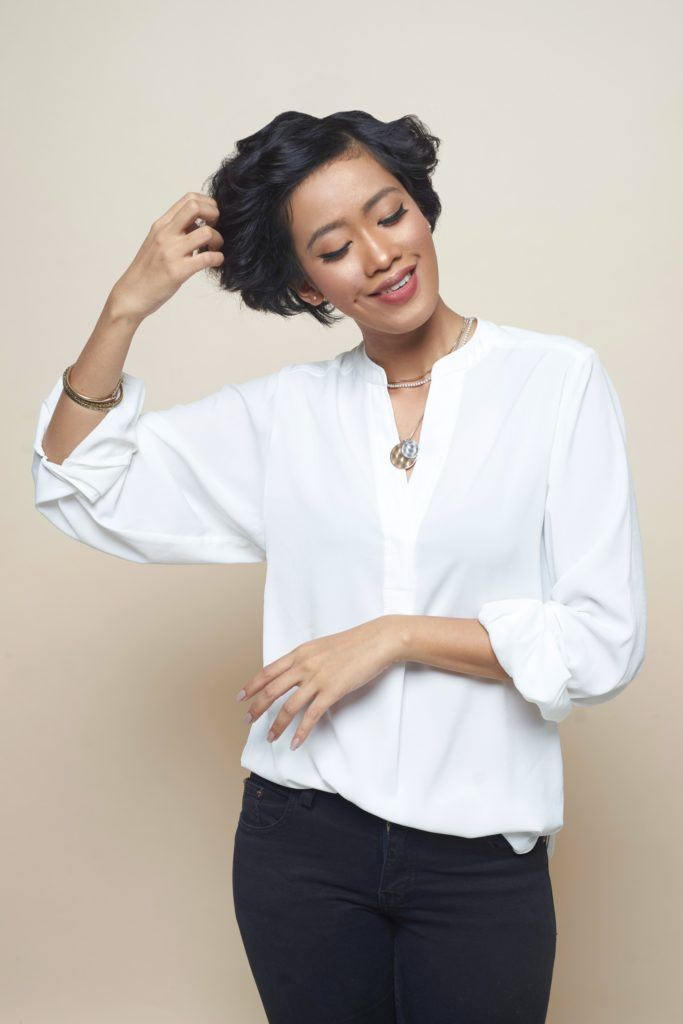 Asian woman finger-combing her short black curly hair wearing a white blouse and black pants