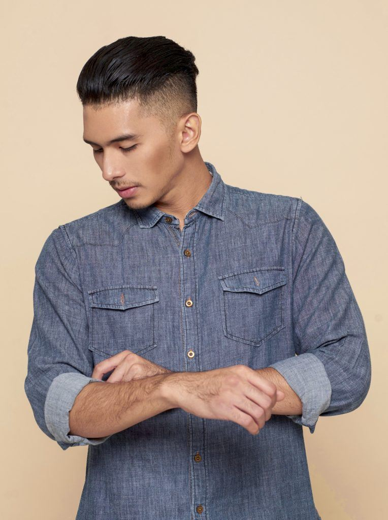 Asian man with a slicked-back undercut hairstyle wearing a denim wash polo