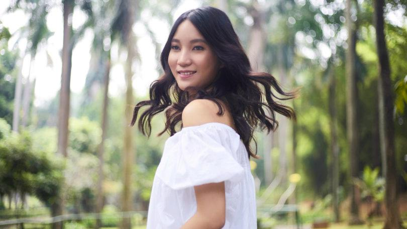Beach waves: Asian woman with long black wavy hair wearing a white blouse outdoors