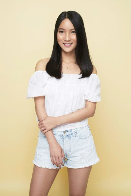 Beach waves: Asian woman with long black hair wearing a white blouse and denim shorts