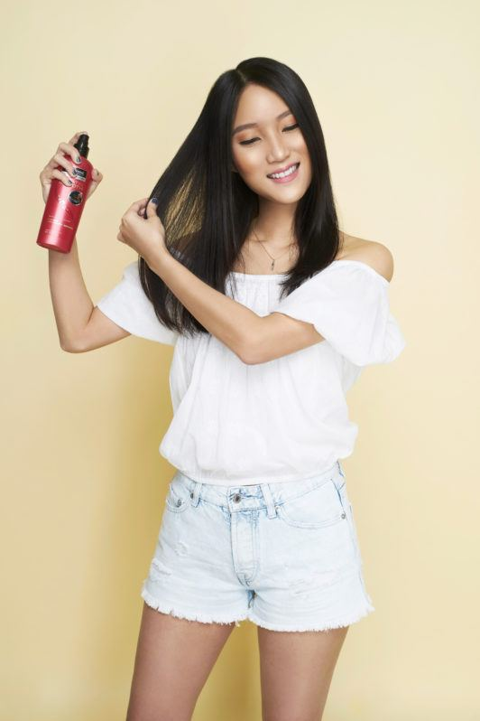Beach waves: Asian woman spraying heat protectant on her long black hair against a champagne-colored background