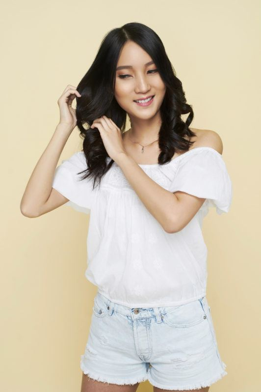 Beach waves: Asian woman finger-combing her long black wavy hair wearing a white blouse and denim shorts