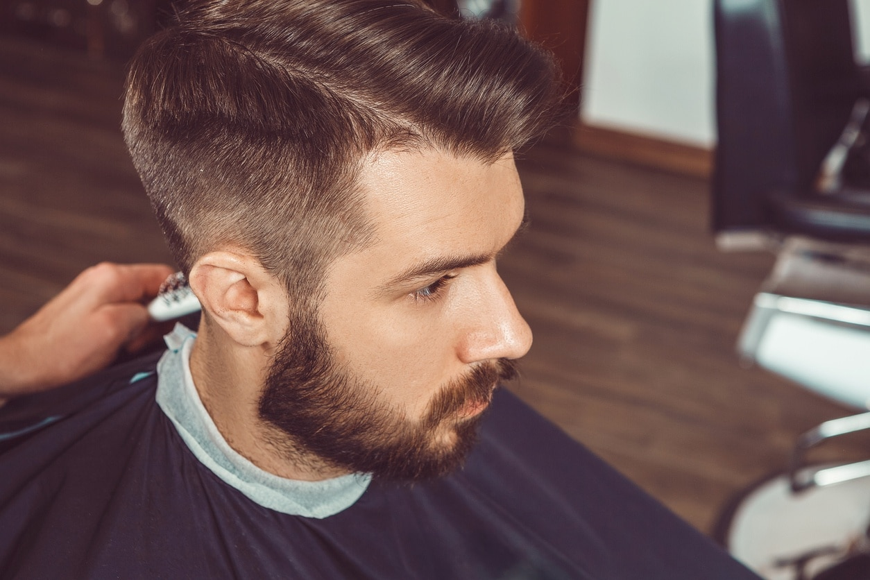 The hands of young barber making haircut of attractive bearded man in barbershop doing a hard part haircut