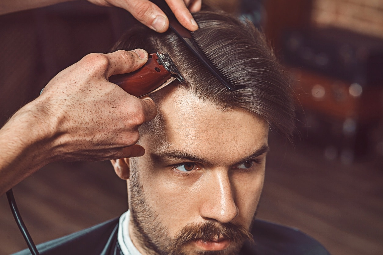 Hipster client visiting barber shop. The hands of young barber making the cut of beard for a hard part haircut