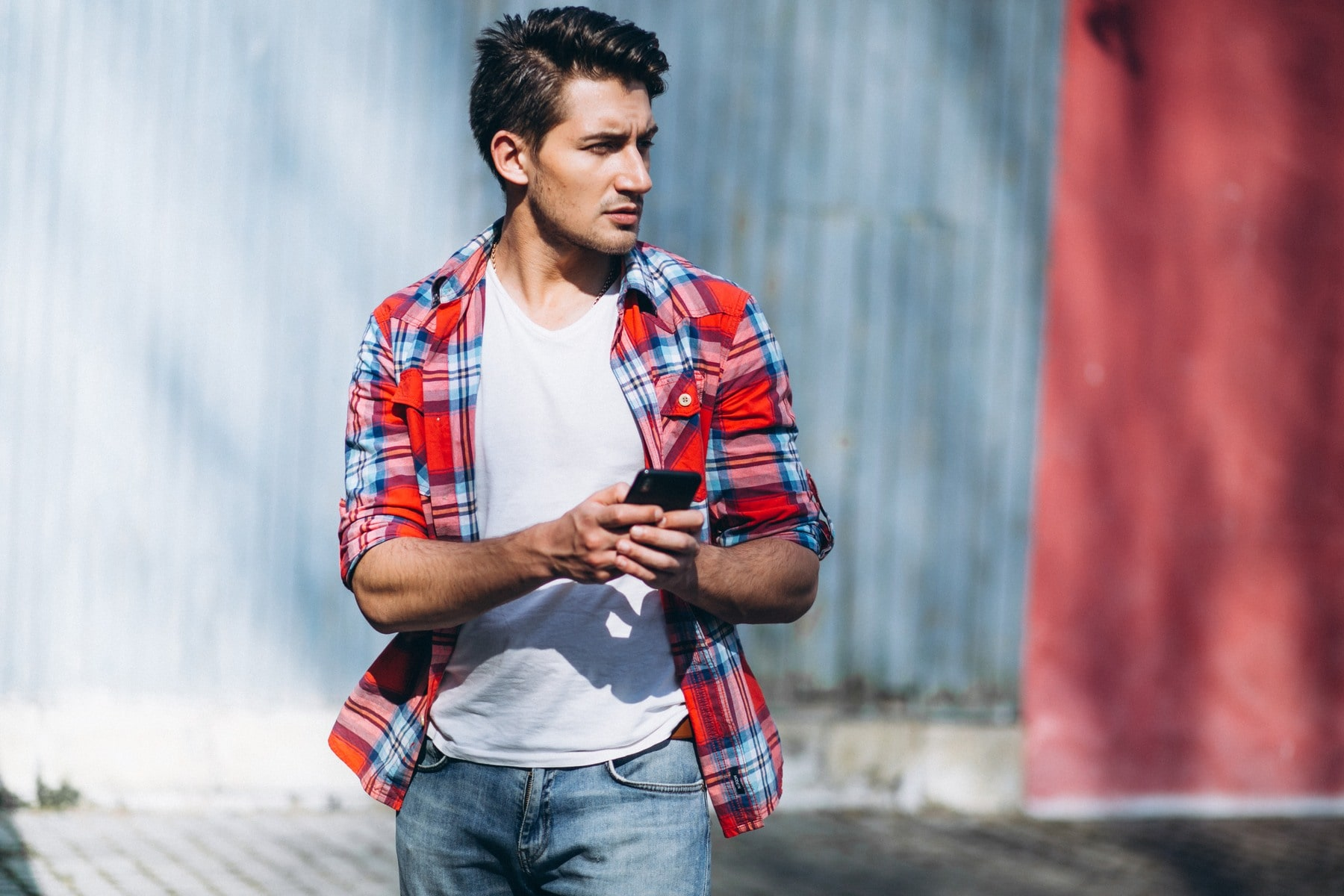 Comb over hairstyles: Man with black hair in comb over hairstyle wearing a plaid polo and white shirt and denim jeans outdoors