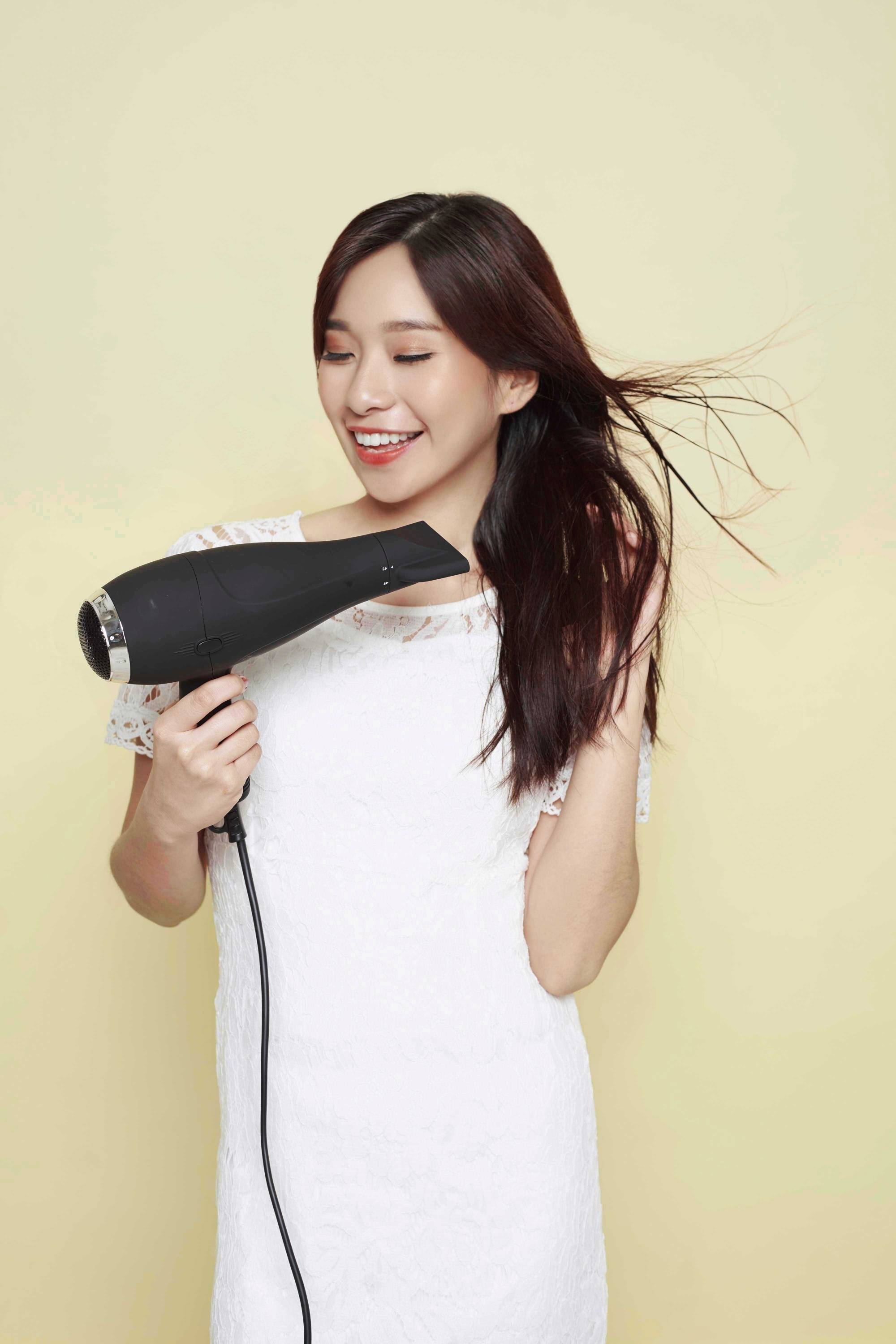 Blow dry your hair: Asian woman blow drying her long dark hair