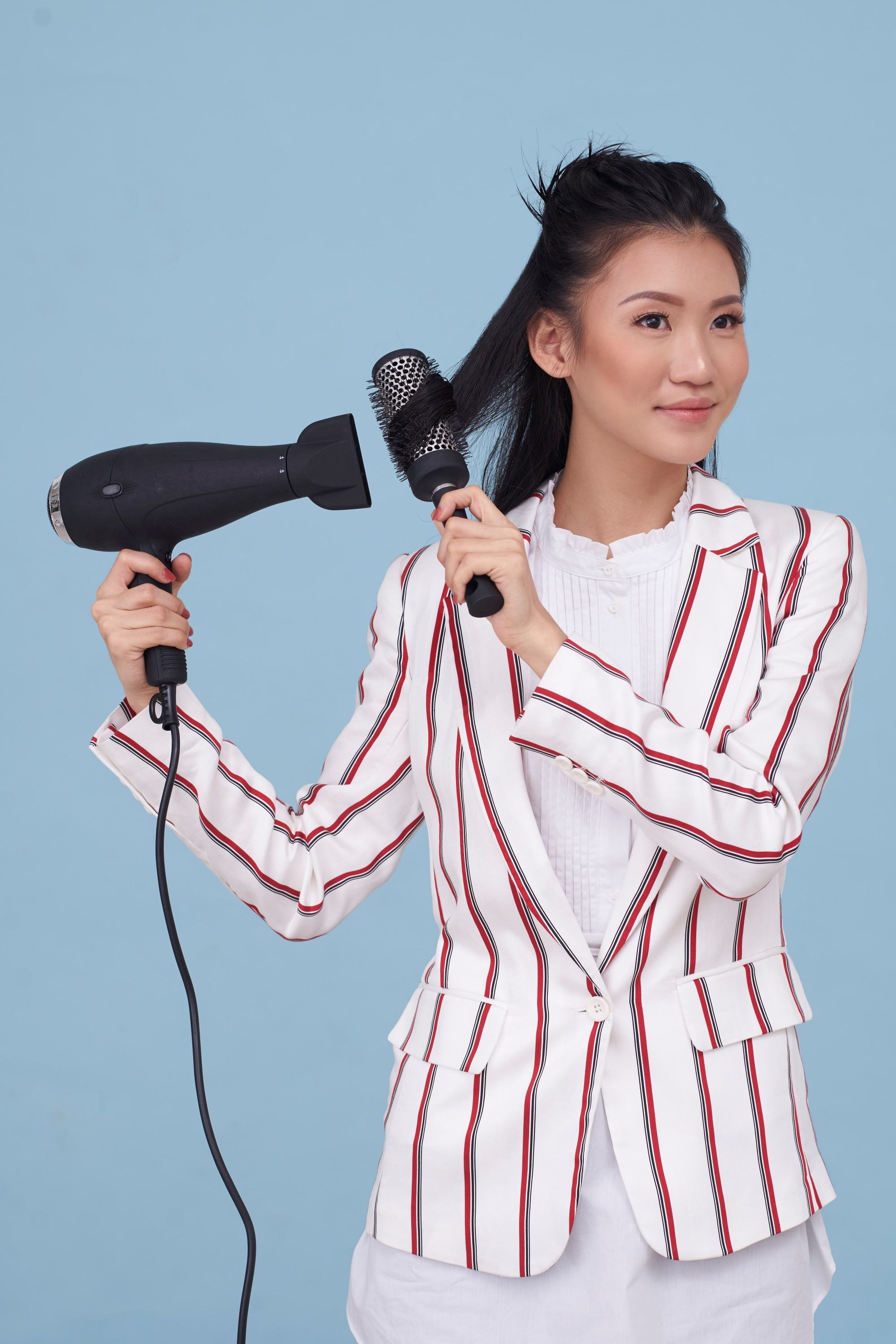 Blow dry your hair: Asian woman blow drying and brushing her medium-length dark hair