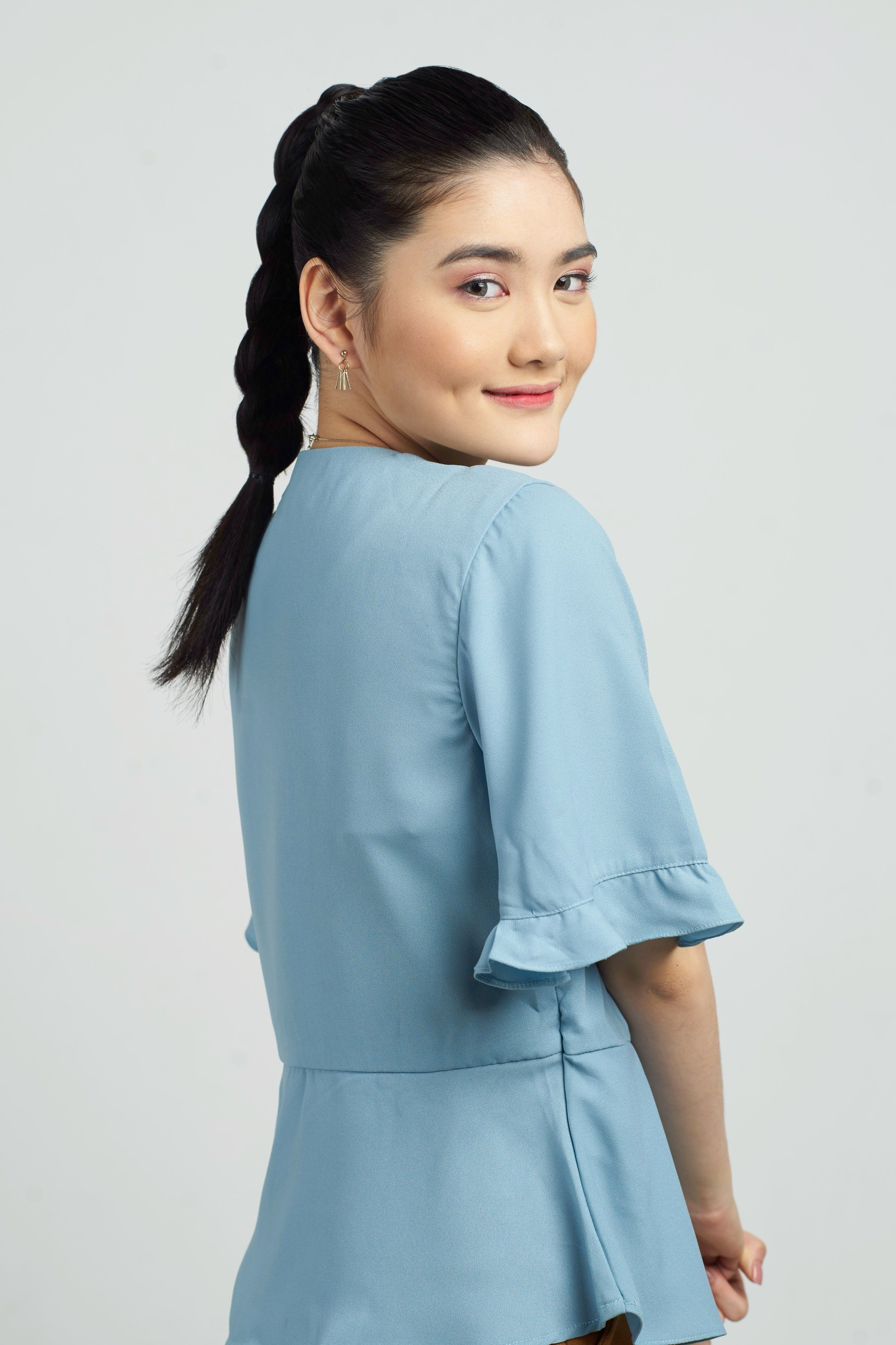 Blow dry your hair: Asian woman with long black hair in a braid ponytail wearing a blue blouse