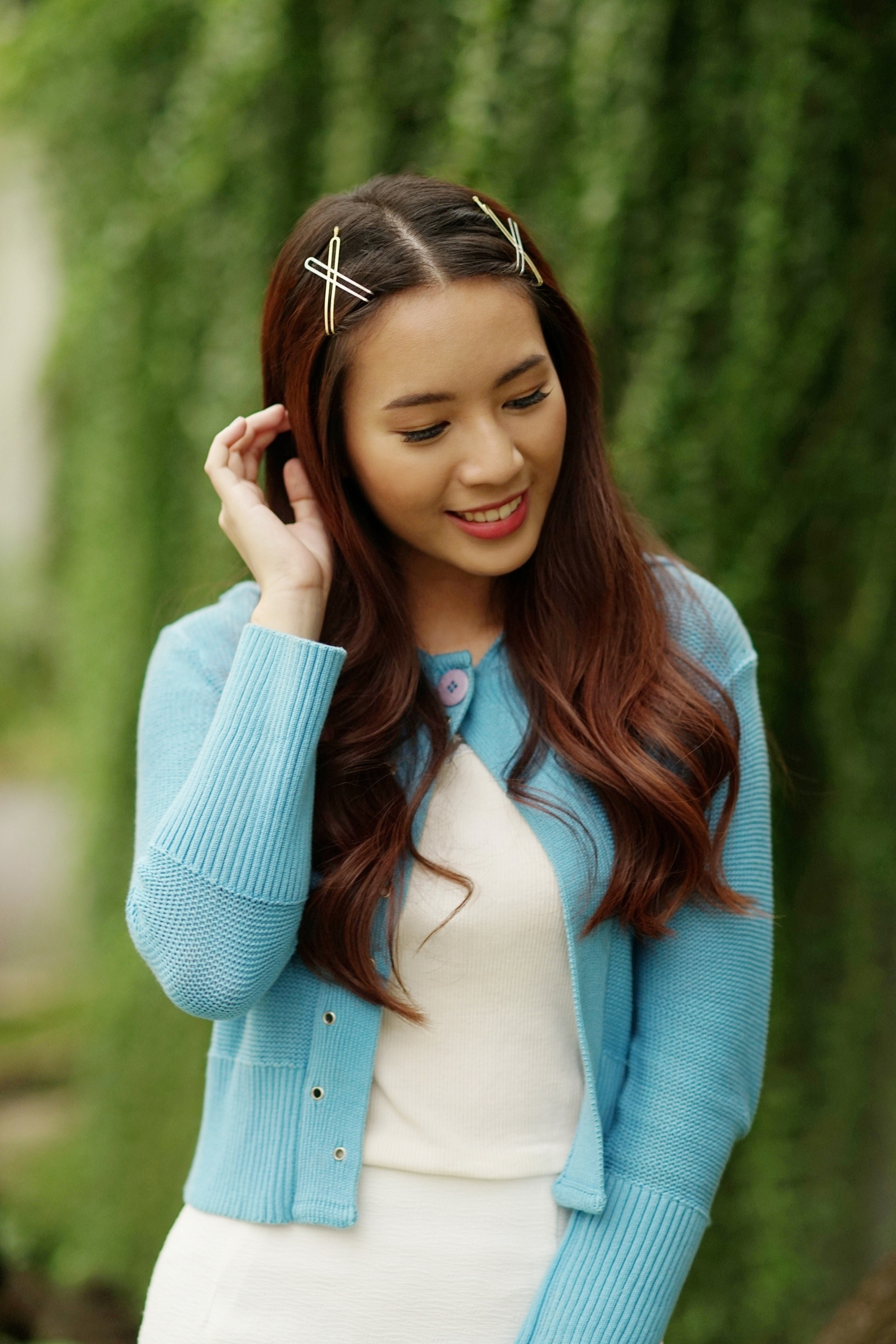 Blow dry your hair: Asian woman with long dark hair with hair clips wearing a dress outdoors