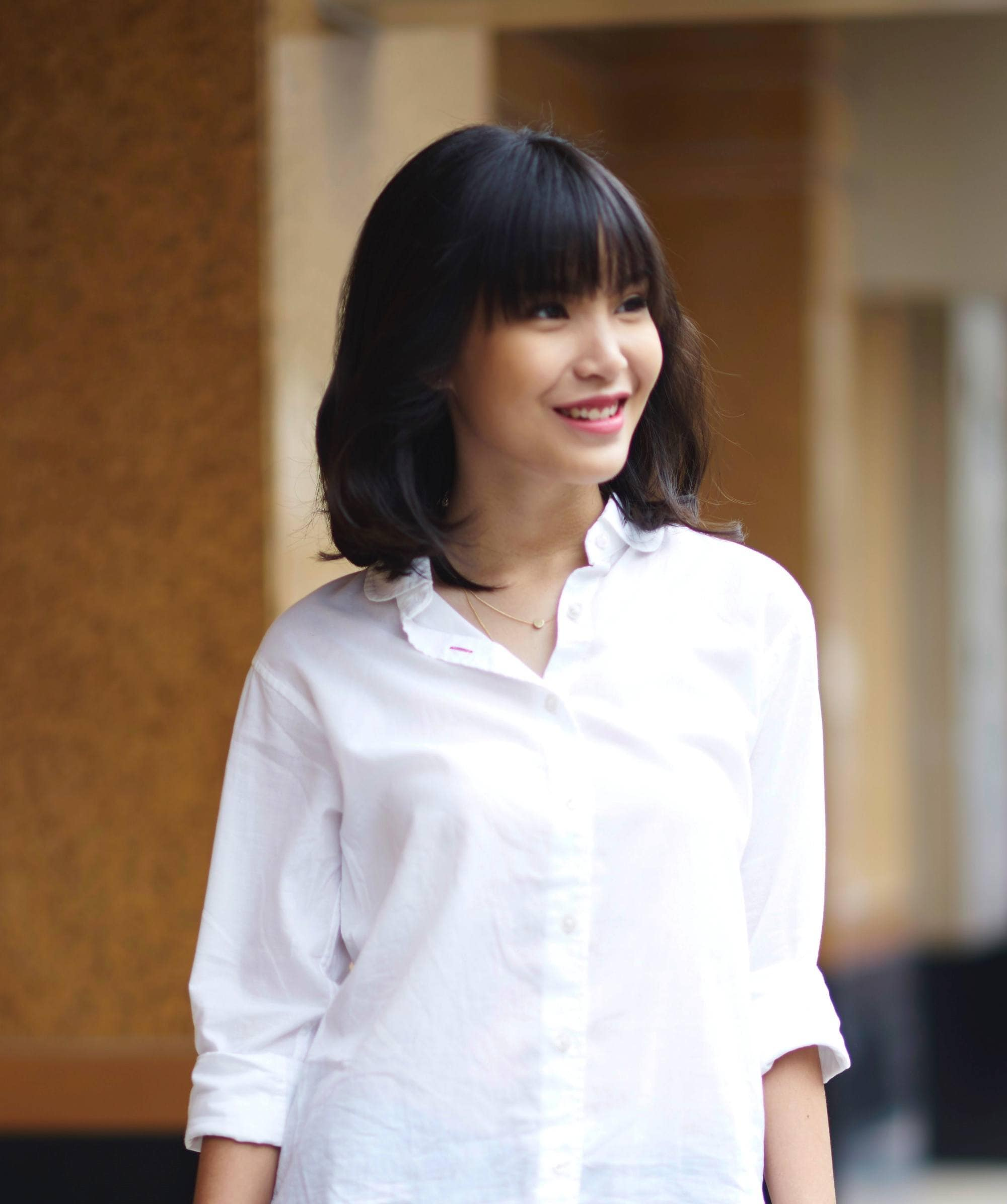 Blow dry your hair: Asian woman with shoulder-length black hair with bangs wearing a white blouse outdoors