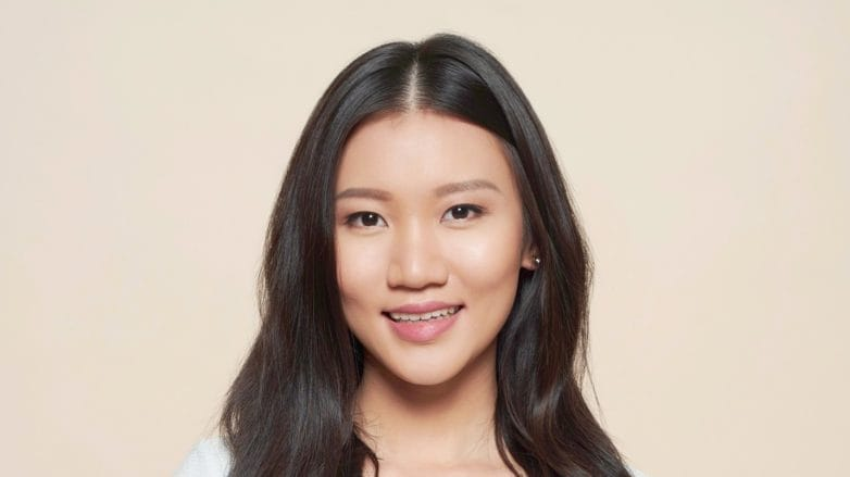 Brush your hair the right way: Asian woman with black shoulder-length hair smiling