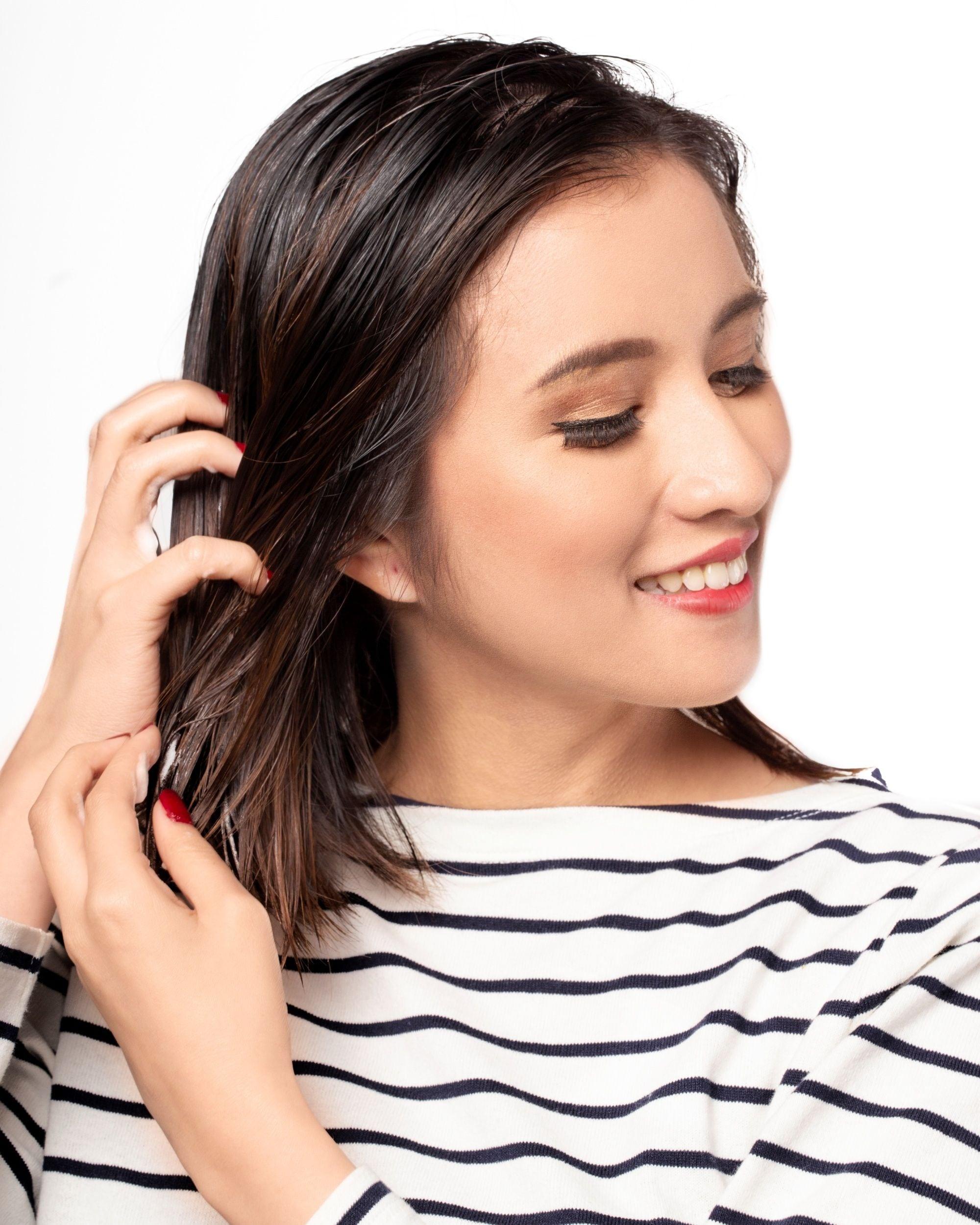 Brush your hair the right way: Closeup shot of an Asian woman finger-combing her short dark hair