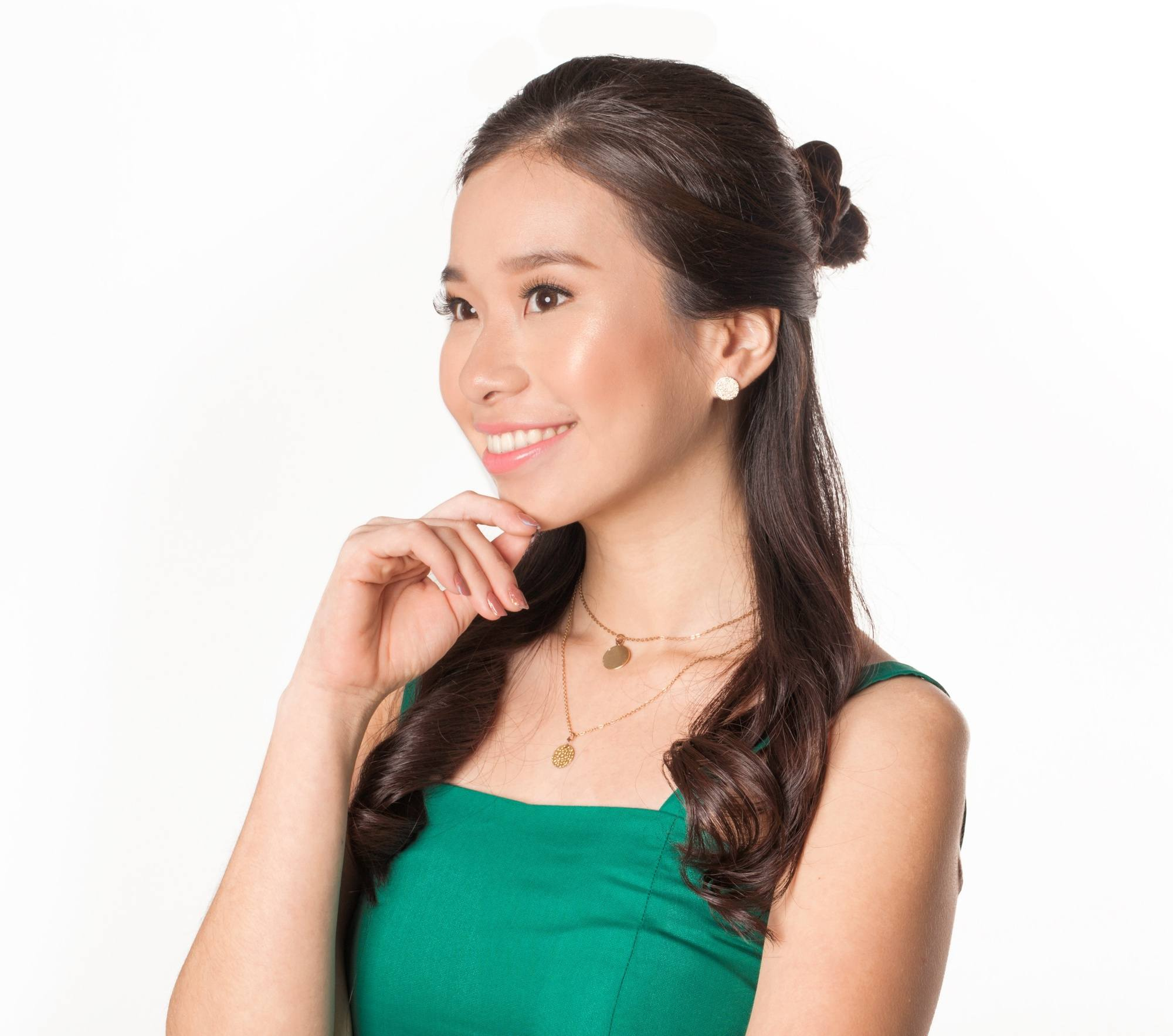 Casual Hairstyles: Closeup shot of an Asian woman with long dark hair in a half updo with bun smiling and wearing a green dress