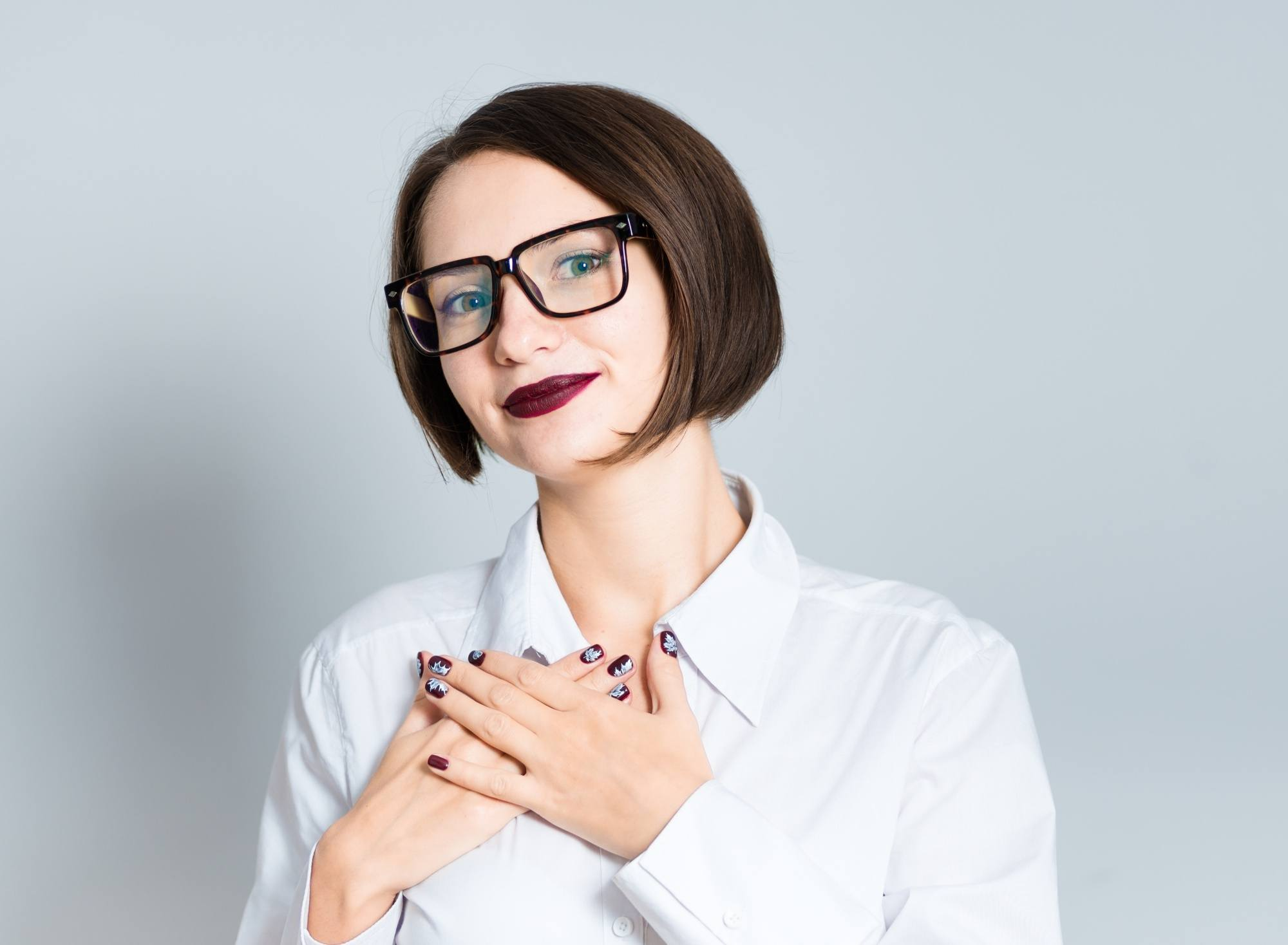 Chin length hairstyles: Woman with short dark brown hair wearing eyeglasses and white blouse