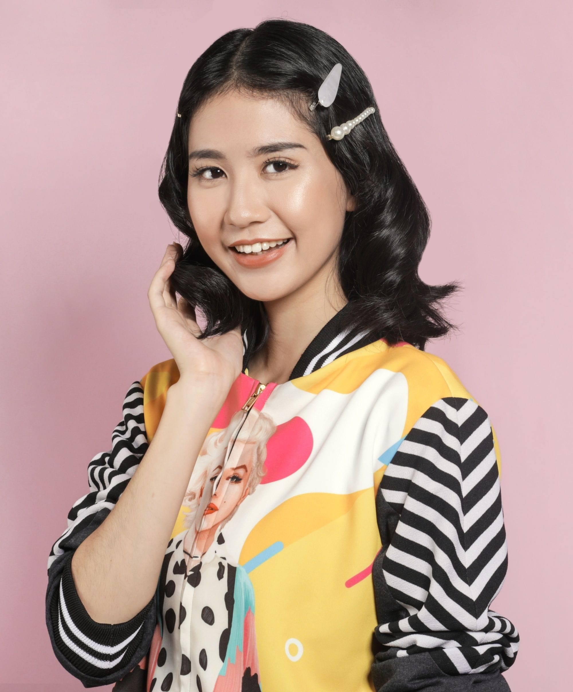 Asian woman with cute hairstyle for short hair wearing a printed jacket and smiling