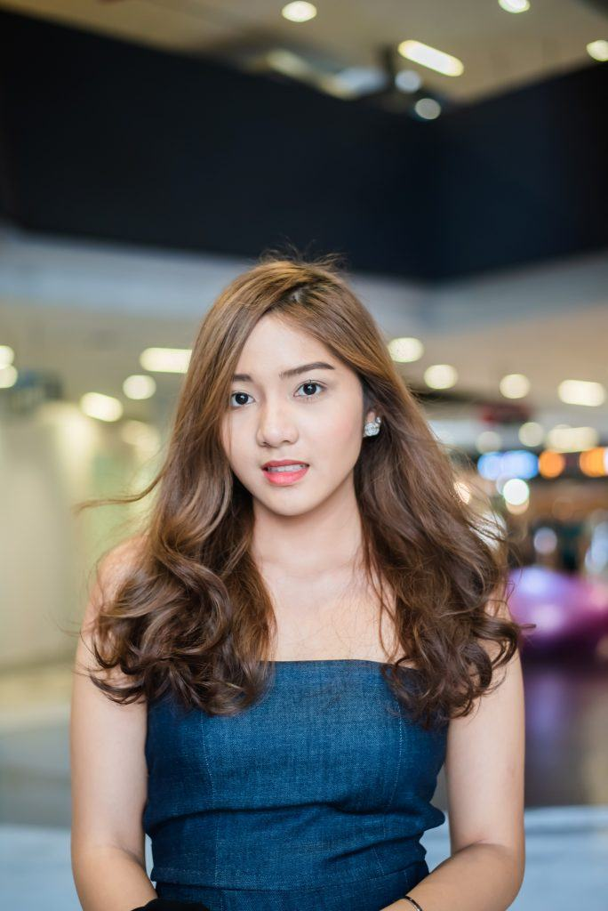 Asian woman with chocolate brown hair color wearing a teal dress