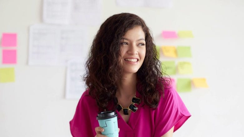 Curly long hair: Asian woman with long dark curly hair smiling wearing a pink shirt