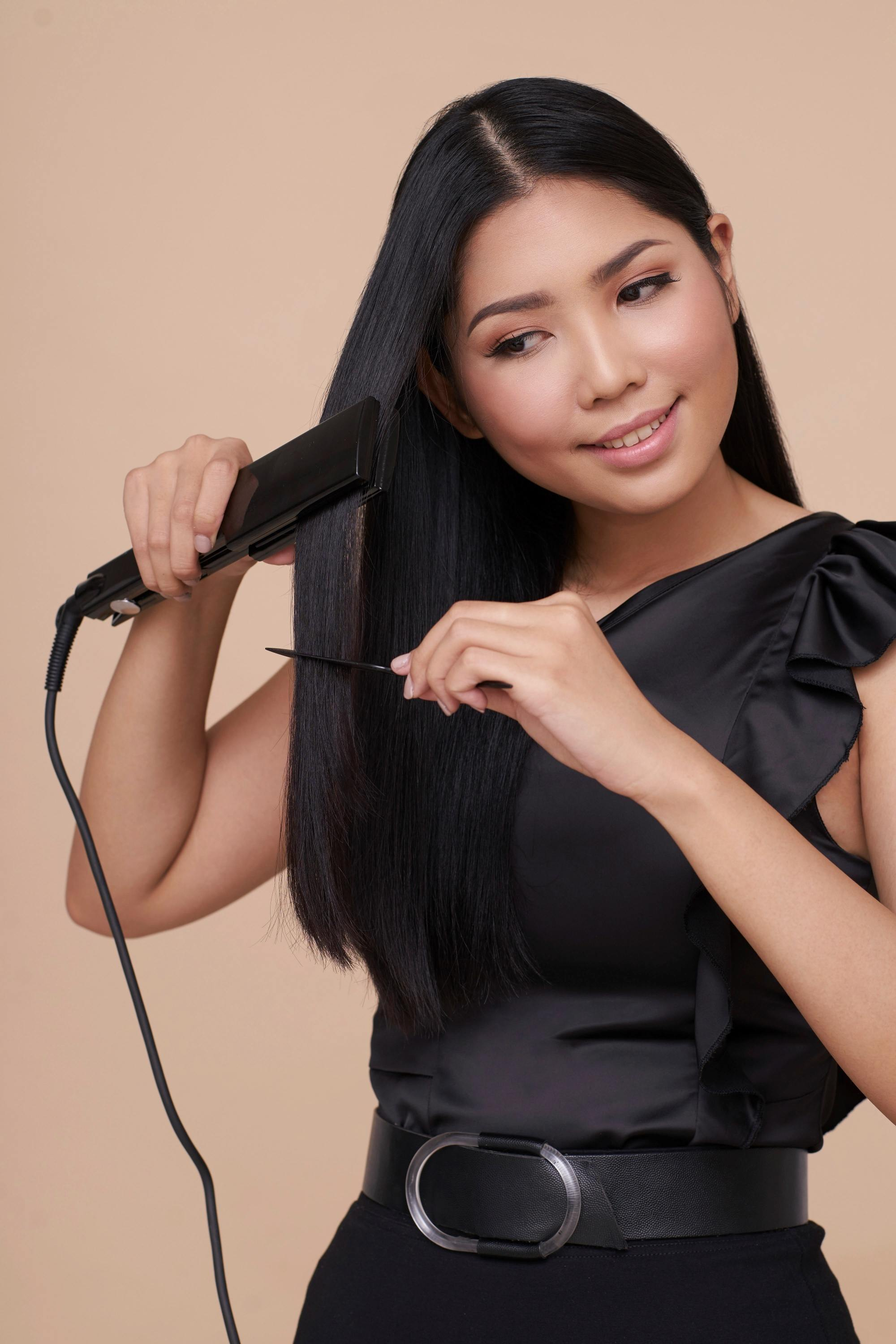 Keratin Smoothing Treatment: Asian woman ironing her long straight black hair