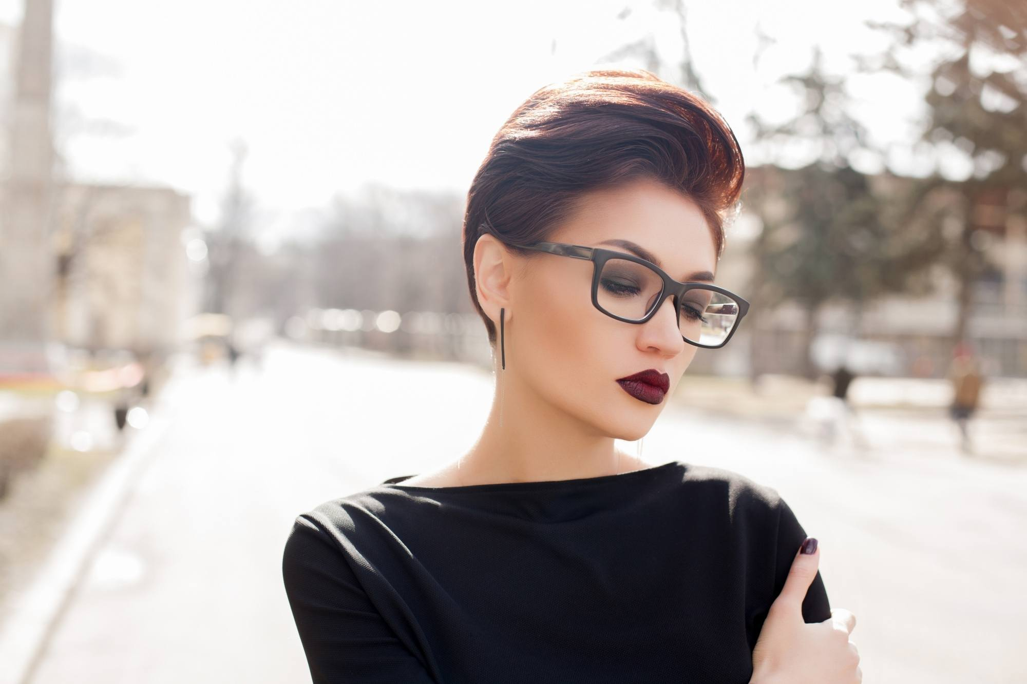 Anti-dandruff shampoo: Closeup shot of a woman with dark pixie cut hair wearing eyeglasses and black top outdoors
