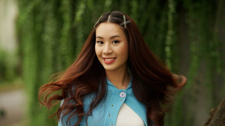 White hair causes: Asian woman with long dark brown hair wearing a white dress and blue cardigan outdoors