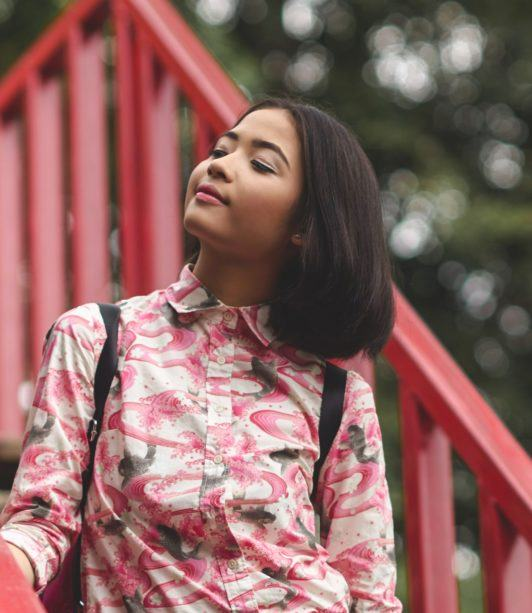 How to style a bob: Closeup shot of an Asian woman with short black hair wearing a printed polo outdoors