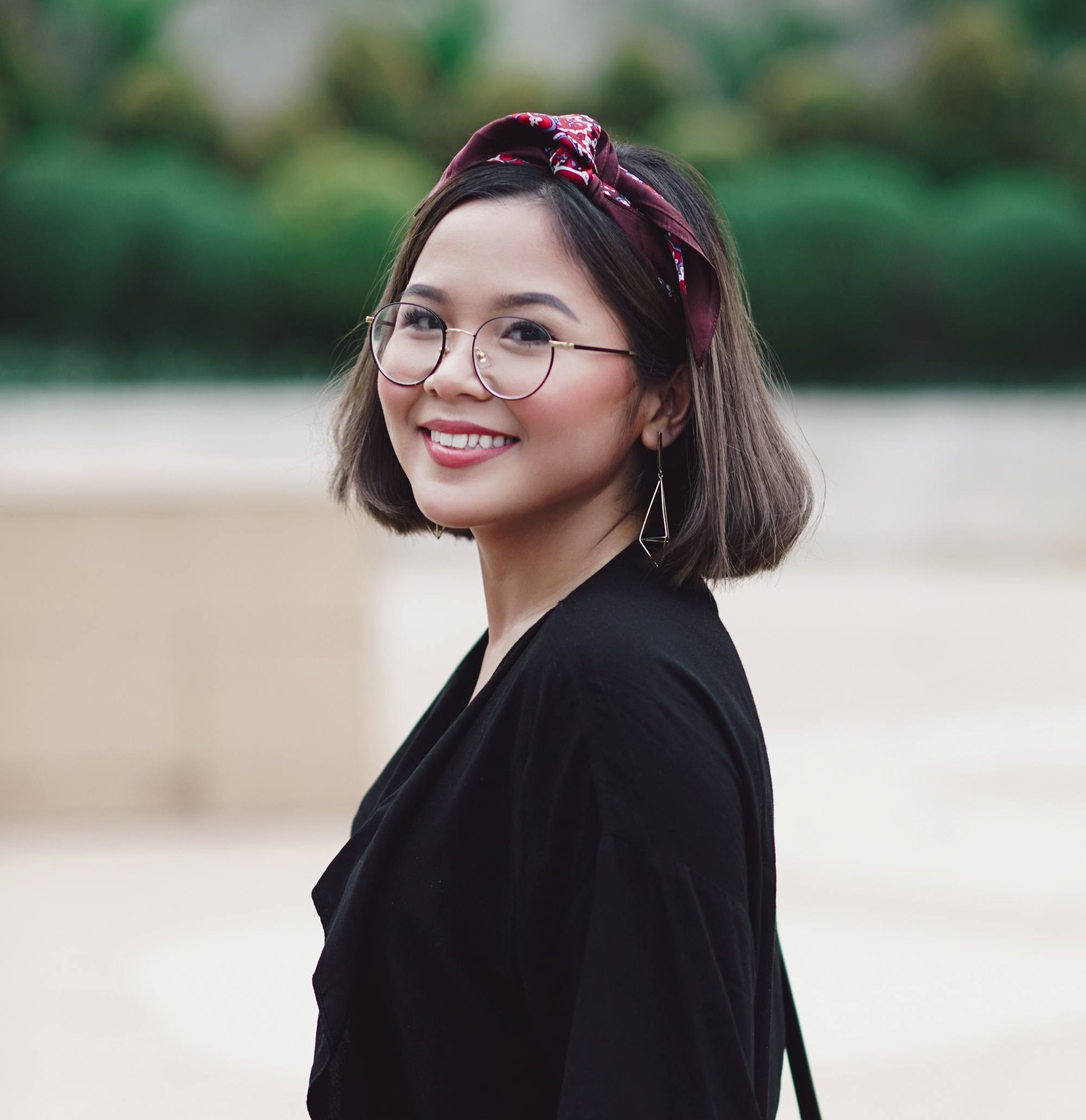 How to style a bob: Asian woman with dark short hair wearing a headband, eyeglasses, and black shirt outdoors