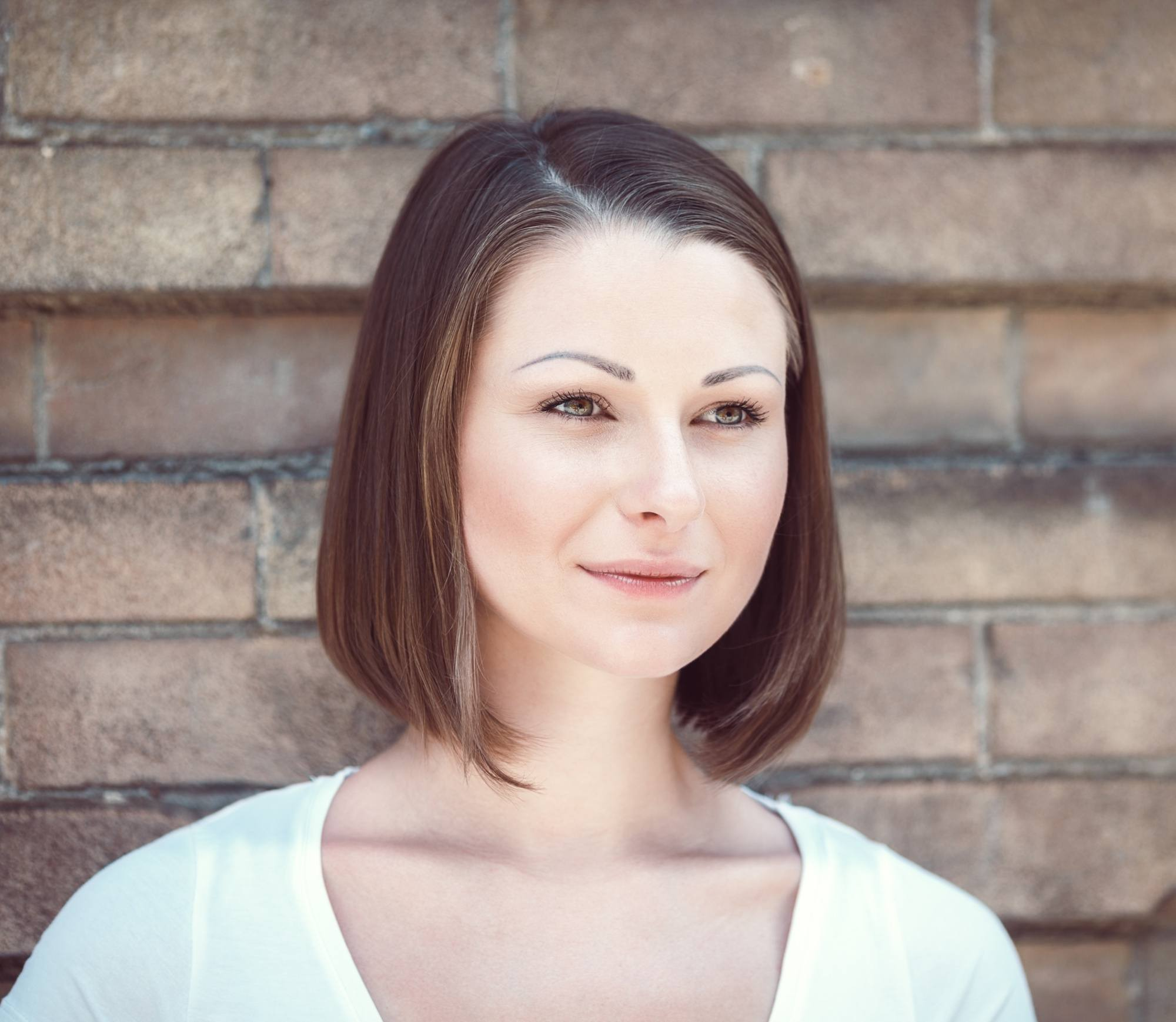 How to style a bob: Closeup shot of a woman with short dark brown hair wearing a white shirt against a wooden background