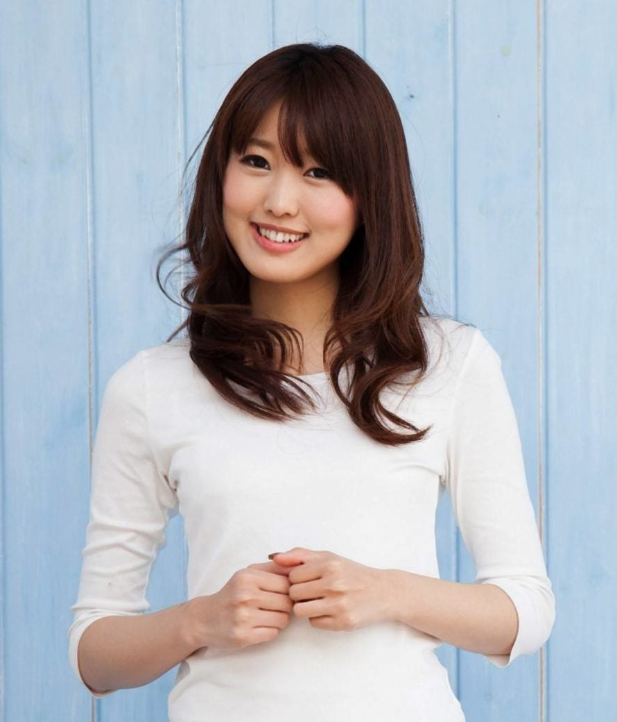 Japanese hairstyles: Asian woman with long dark brown layered hair with bangs wearing a white shirt
