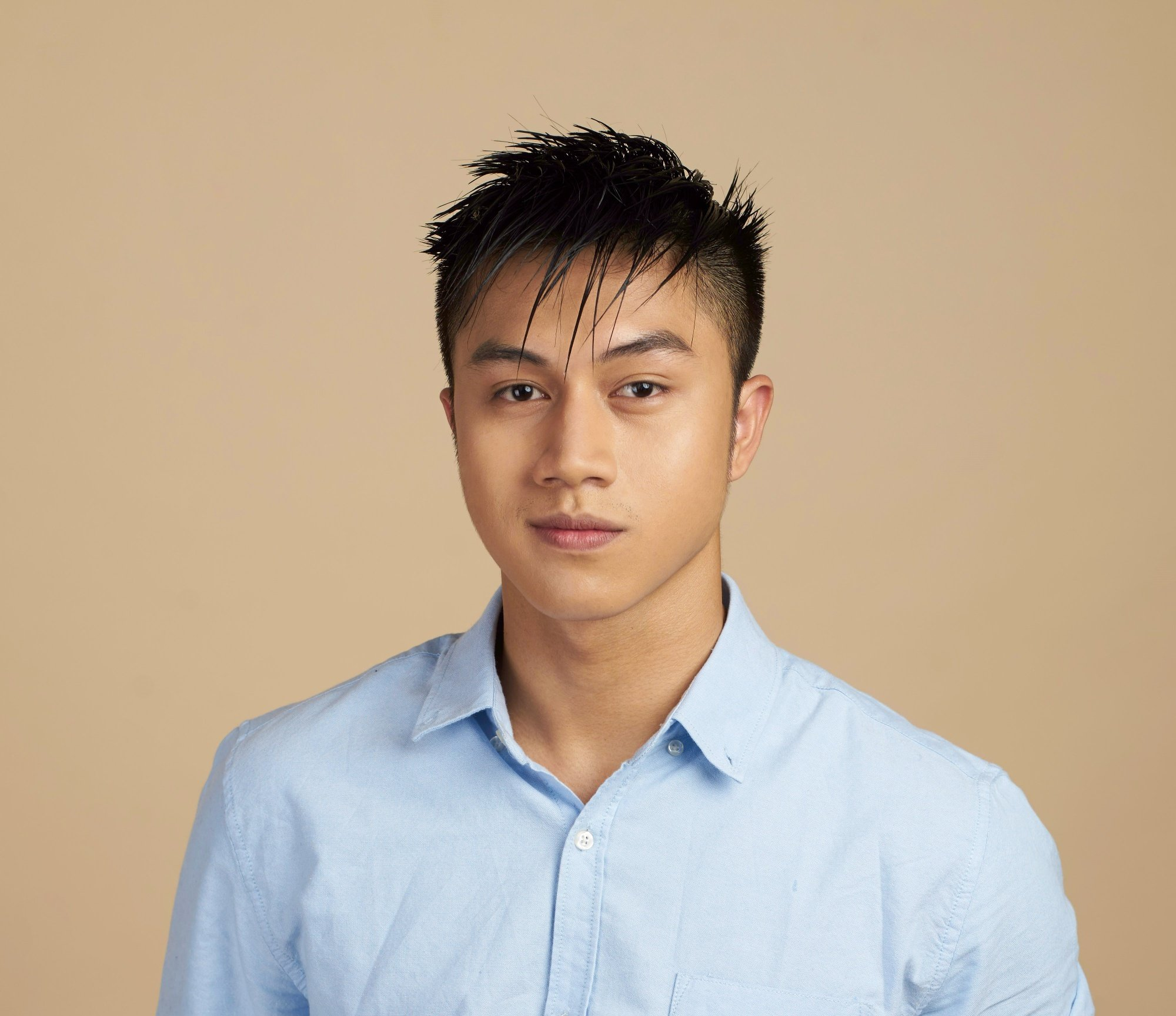 Men's grooming: Closeup shot of an Asian man with short black wet hair wearing a blue polo