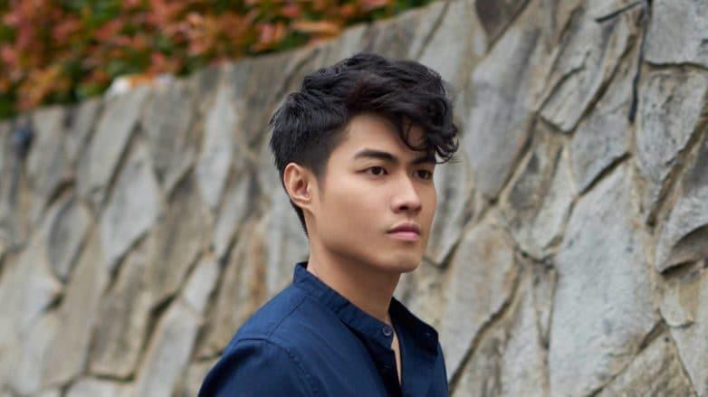 Men's grooming: Closeup shot of an Asian man with short black wavy hair wearing a dark blue polo outdoors