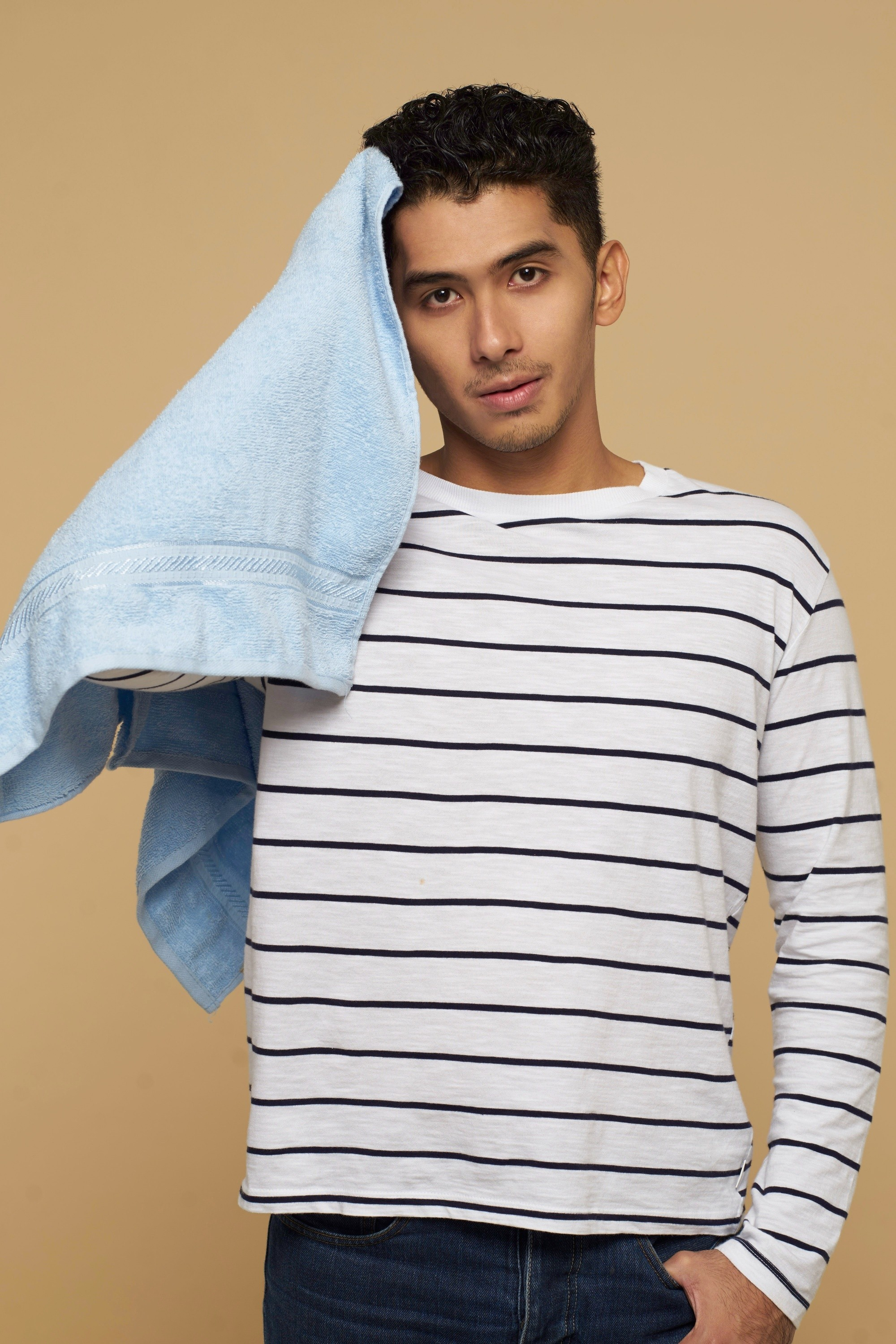 Asian man holding a blue towel and patting his short black hair dry