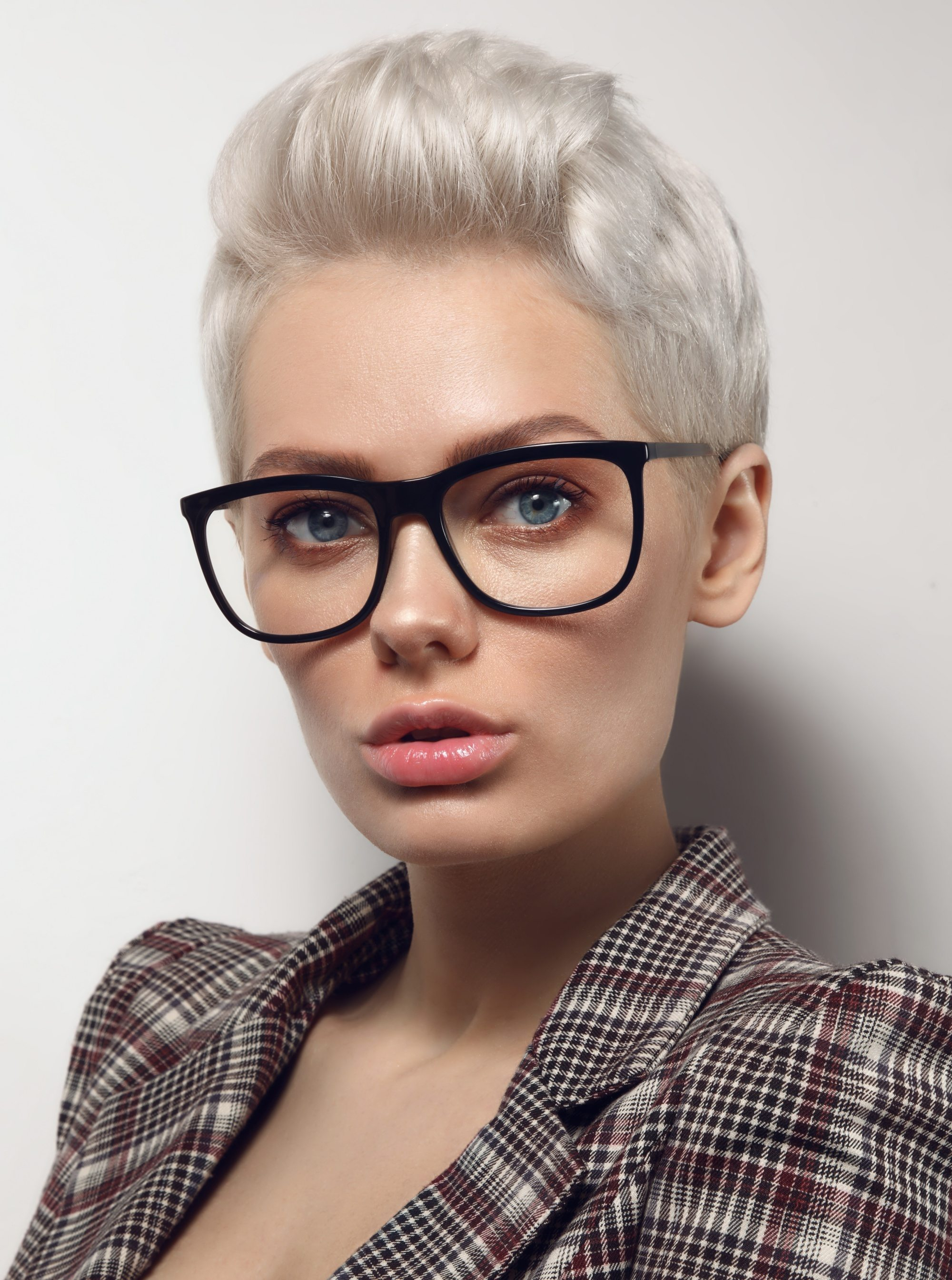 Woman with platinum blonde pixie cut wearing eyeglasses