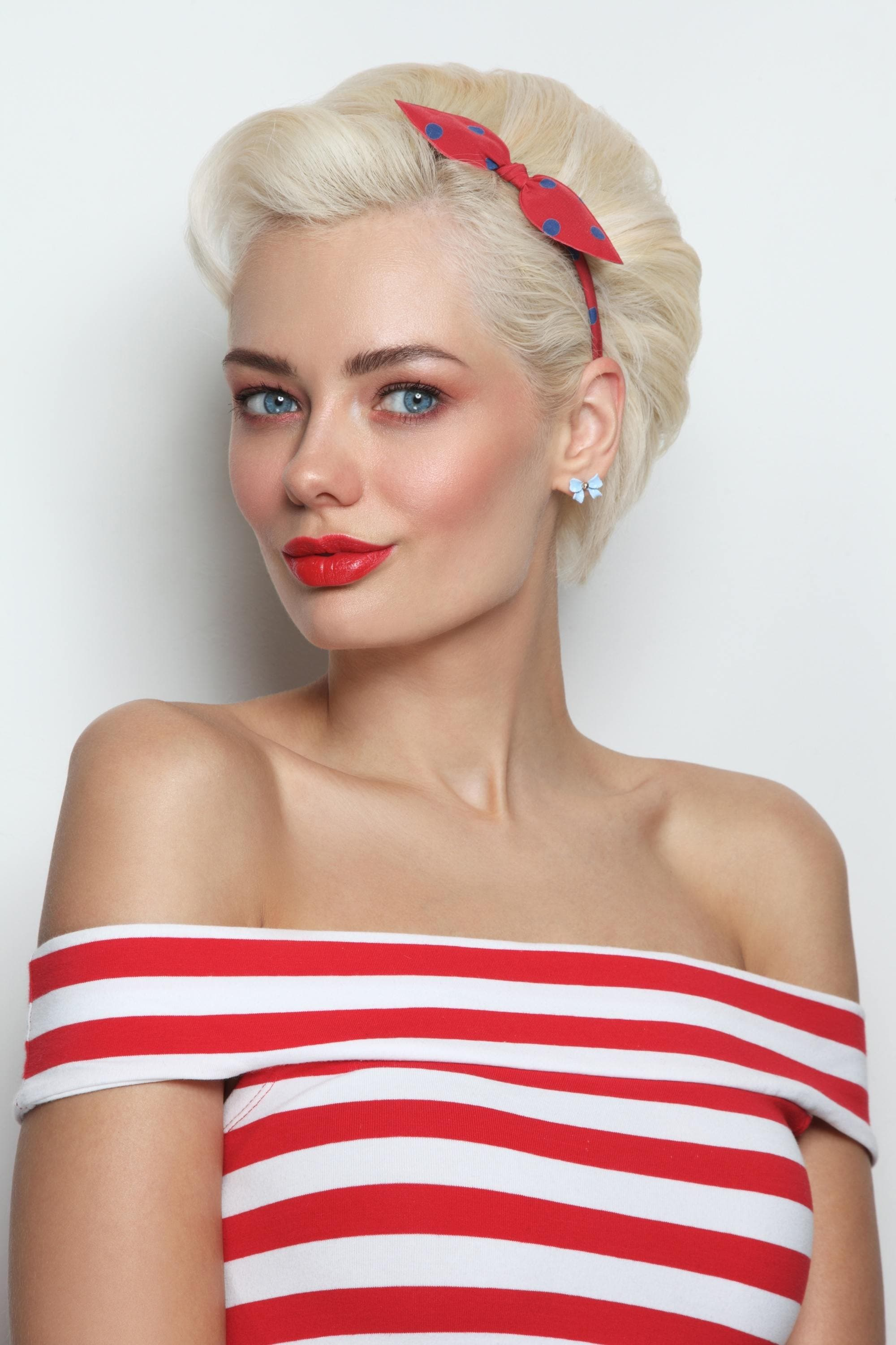 Woman with platinum blonde pixie cut with red headband wearing a striped red top