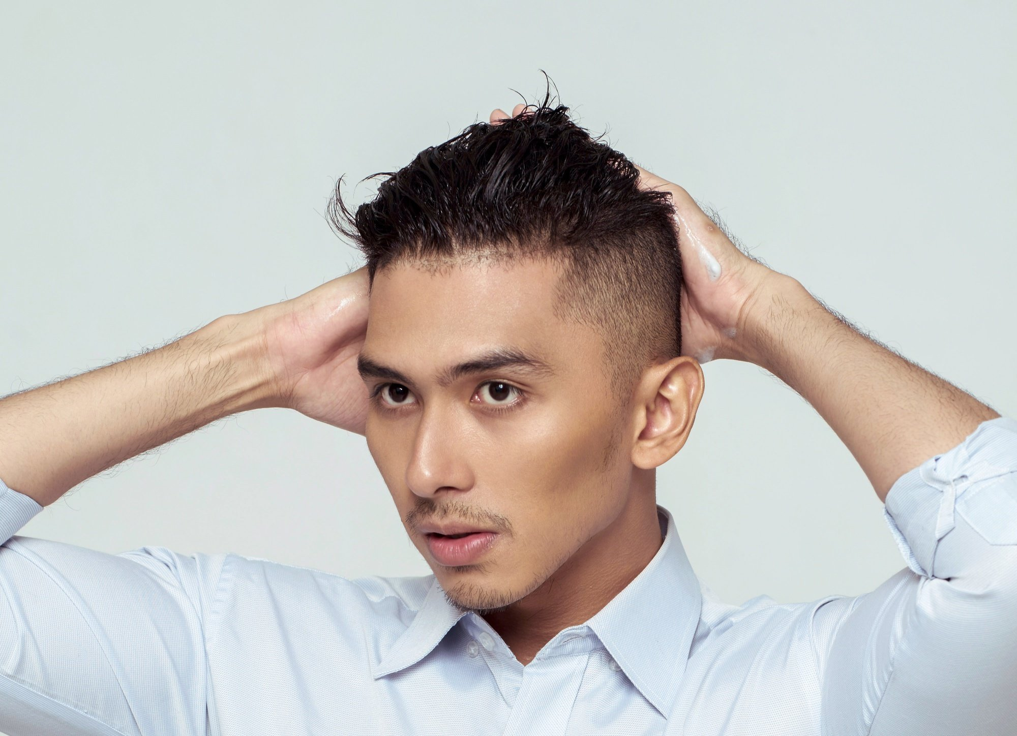 Scalp care men: Closeup shot of an Asian man massaging his scalp