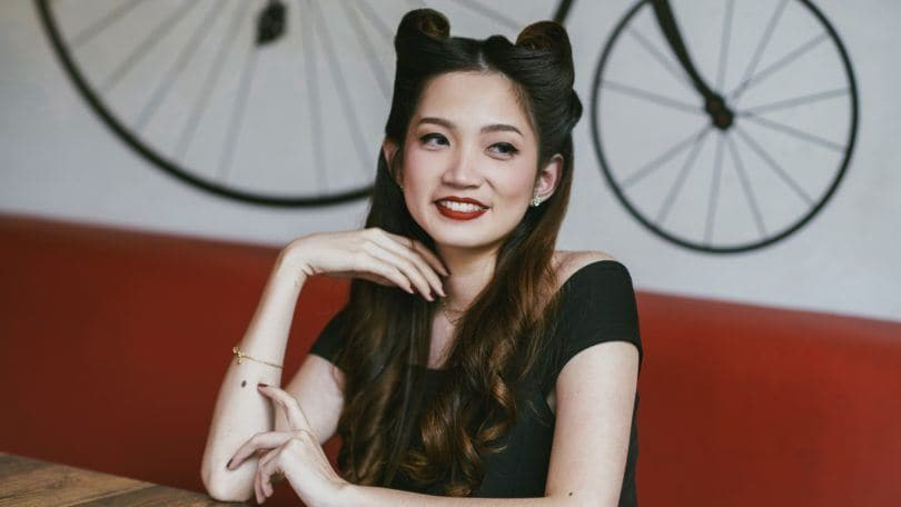 Victory rolls: Asian woman in a cafe with long dark hair in victory rolls