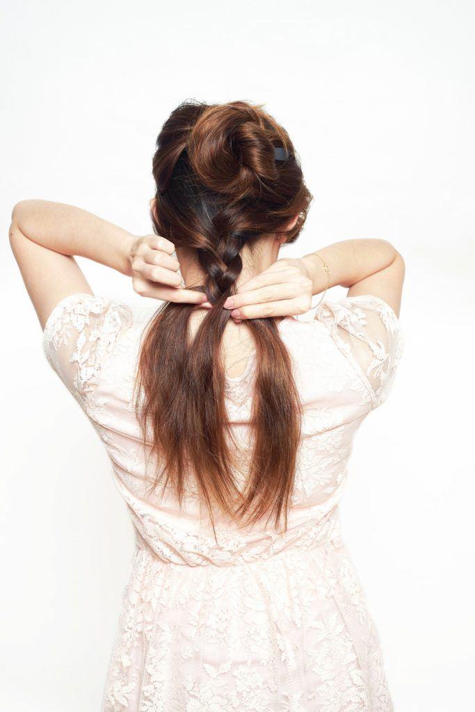 Back shot of an Asian woman braiding her hair
