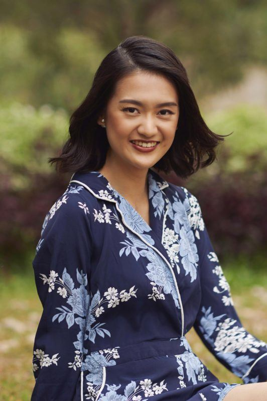 White hair causes: Asian woman wearing a floral coords, smiling