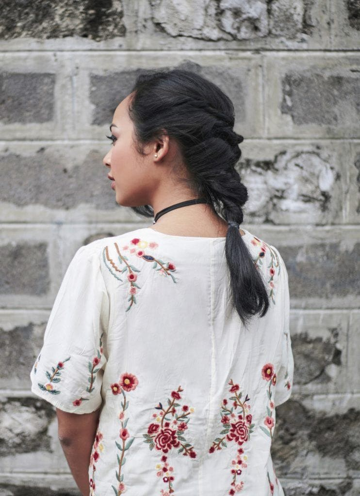 Boho hairstyles: Bach shot of an Asian woman with long black hair in boho flip in braid wearing a dress outdoors