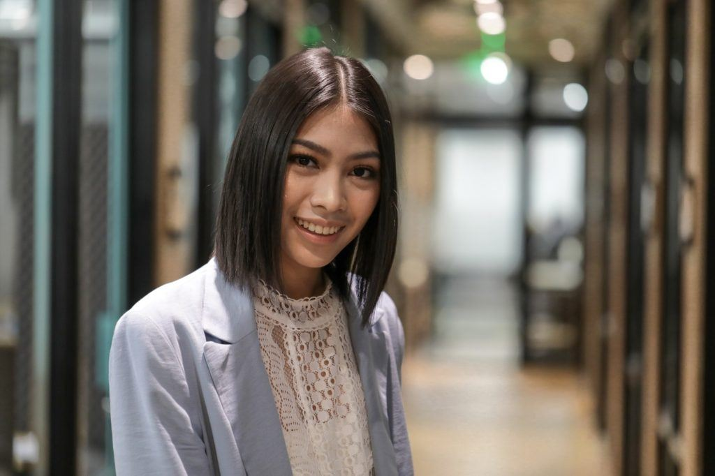 Easy hairstyles for medium hair: Asian woman with straight center part medium bob wearing a light blue blazer