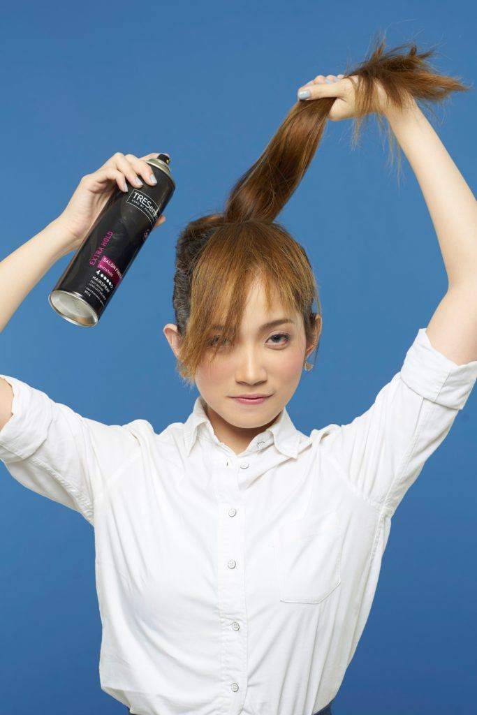 Making faux bangs 4: Asian woman spritzing hairspray on her ponytail
