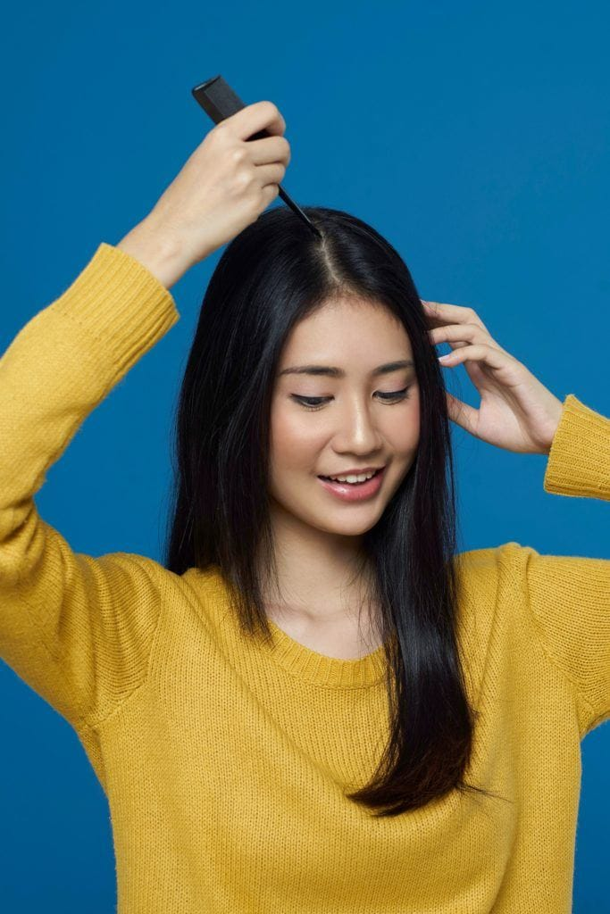 Asian woman parting hair at the center with a comb