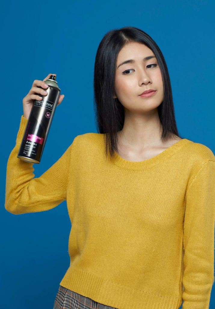 Asian woman spraying hairspray on long hair