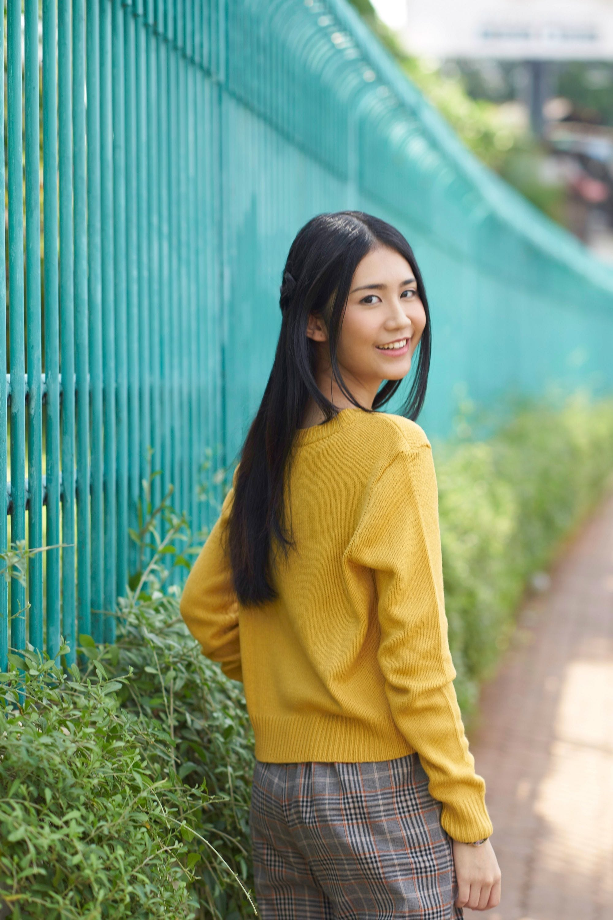 Benefits of aloe vera for the hair: asian woman with long, shine black hair, wearing a yellow sweater