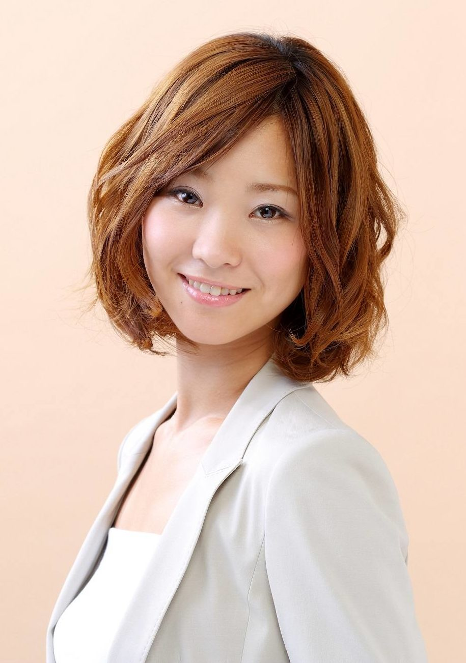 Short straight hairstyles: Asian woman with brown wavy bob and side swept bangs