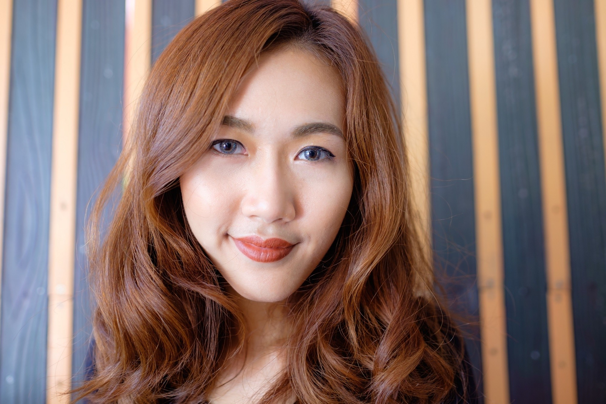 Short straight hairstyles: Asian woman with long brown wavy hair and side swept bangs